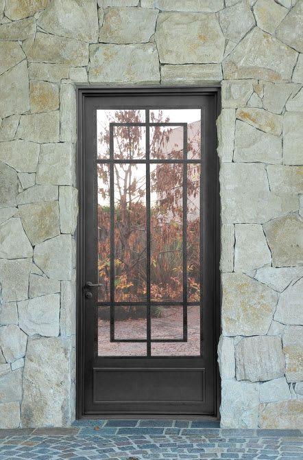 Puerta de hierro en fachada con piedra rustica casas de for Puertas para casas rusticas
