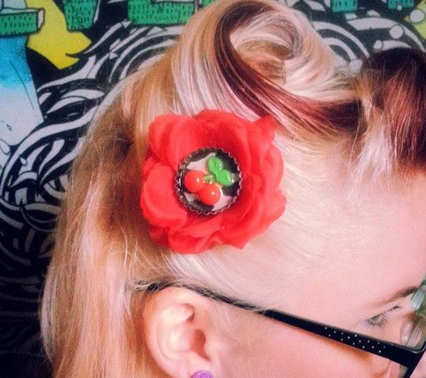 Red Cherry Hair Flower by Sins 'n Needles - This pretty little hair flower is bright red, features a recycled bottle cap center with cherry, comes in your choice of white or grey leopard background, and is securely fastened to a silver tone alligator clasp. Measures approximately 3 inches across.