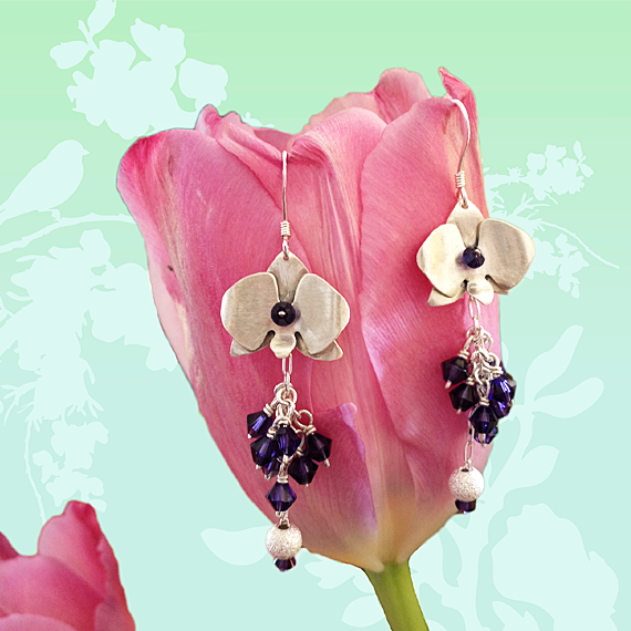 These Orchid inspired earrings are handmade from a sterling silver sheet and purple Swarovski bicone crystals. During the Victorian era, orchids were a symbol of luxury and through the years have also become a symbol of love, beauty, and strength. Elegant and chic, these earrings are a must-have for those that appreciate the beauty of these exotic flowers. Hanging from fish hook earrings, the Orchid Earrings have a brushed stain finish and hang approx. 2 inches from the earlobe.