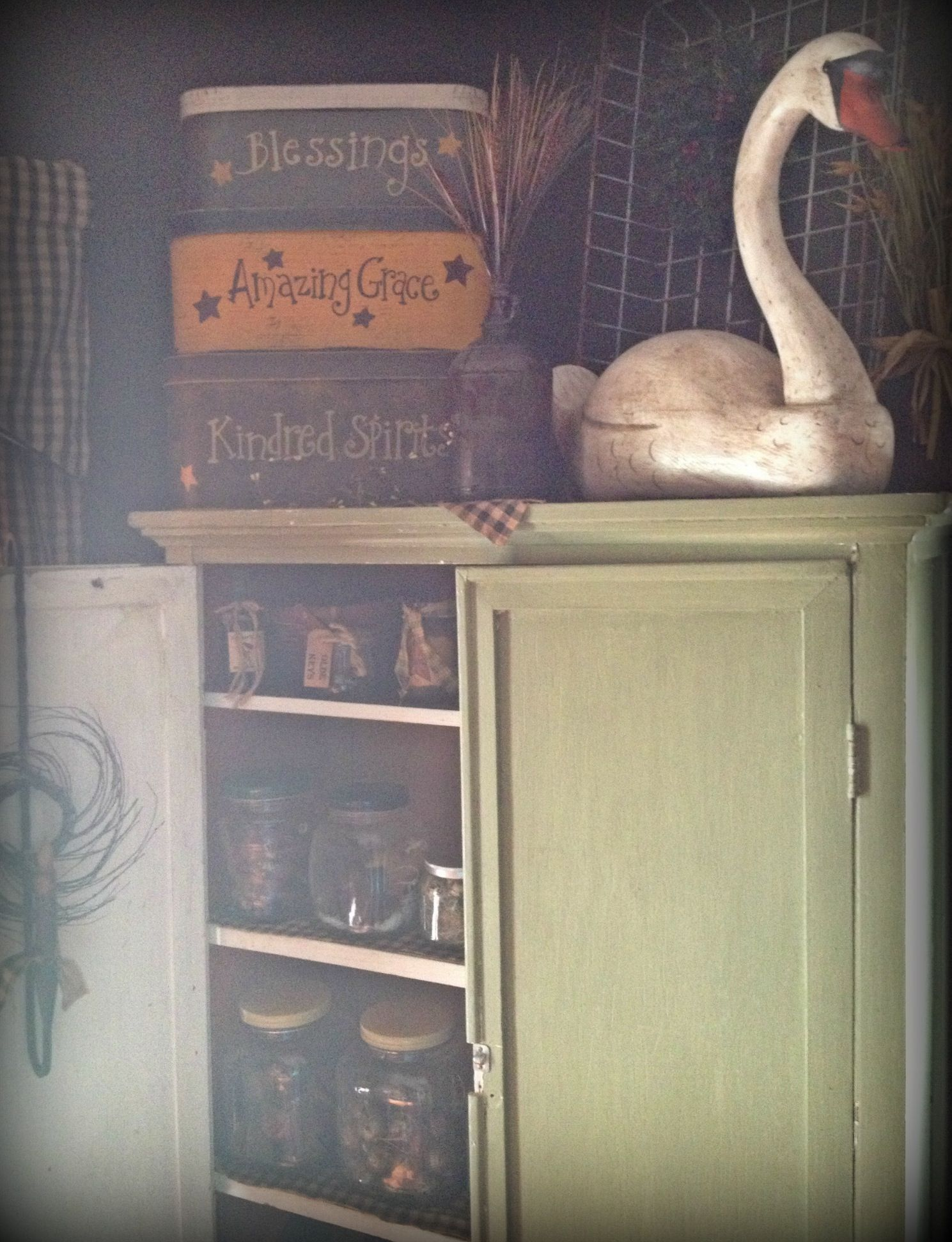 Old green primitive cupboard I use to house my craft stuff. Topped w wooden antique swan decoy. Ye olde crow primitives