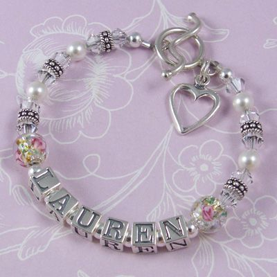 Child Name Bracelet - C12   This bracelet design features gorgeous floral glass beads either side of the name, Swarovski crystals and pearls and Bali sterling silver. This picture shows the C12 design with the curved bar toggle clasp and open heart charm – large letter blocks. Crystal colour - clear. Pearl colour – white.   Either a lobster clasp or toggle clasp may be chosen for this bracelet.