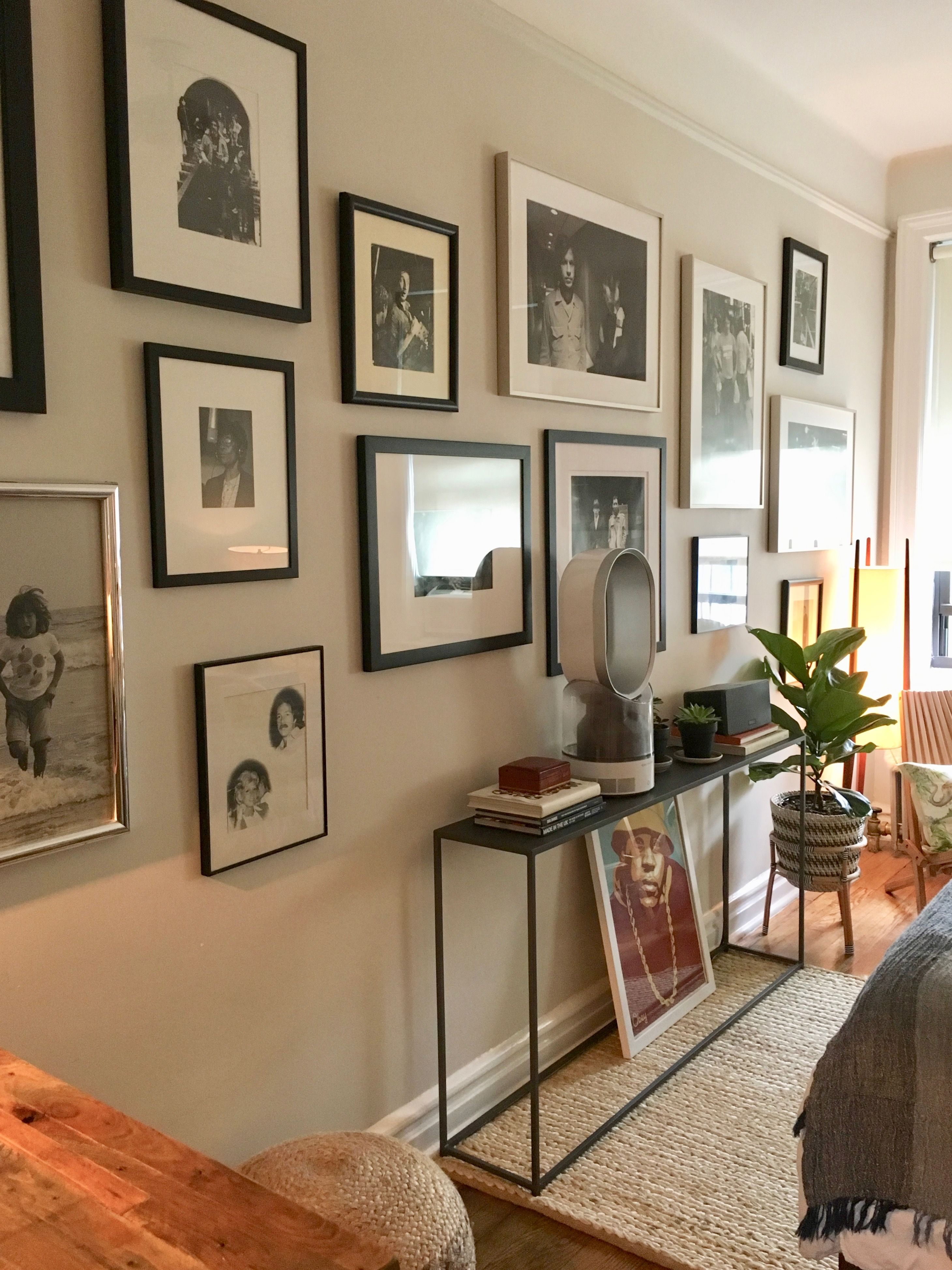 Black and white photography gallery wall in west village bedroom with cb2 console designed and styled by professional organizer laura cattano