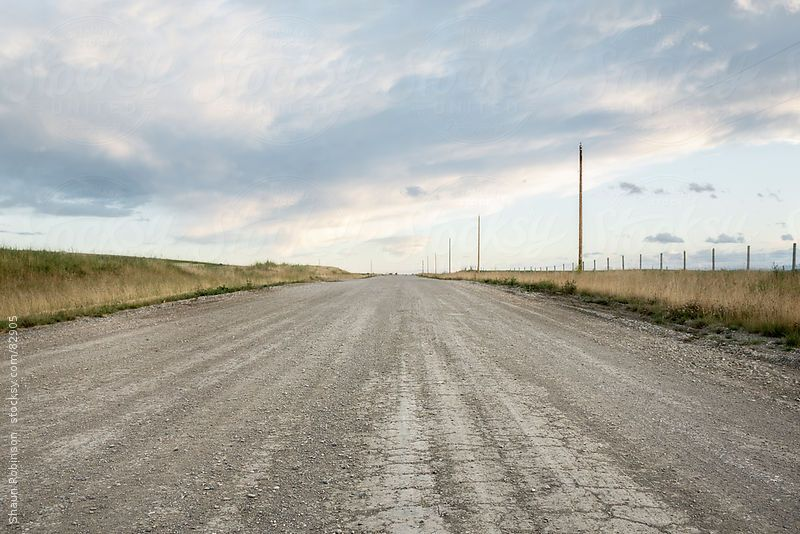 a gravel road in the country with a big sky by Shaun Robinson