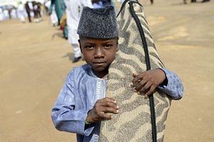 Jos, Nigeria A young boy arrives with his prayer mat at Isa Kazaure praying ground