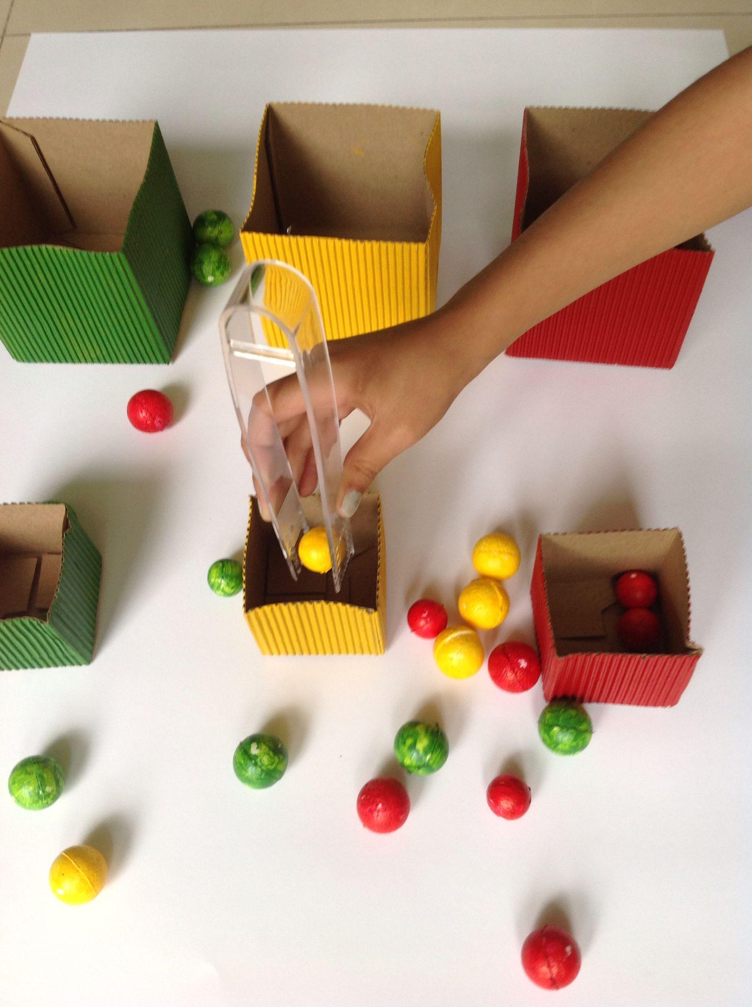 Clasificación por tamaño y color con cajitas de cartón y pelotitas de unicel. Uso de pinzas.