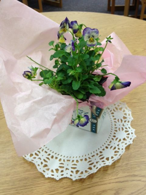Make a very quick, inexpensive and easy centerpiece with an empty teabox, tissue, doily and your favorite annual from a flat of flowers.
