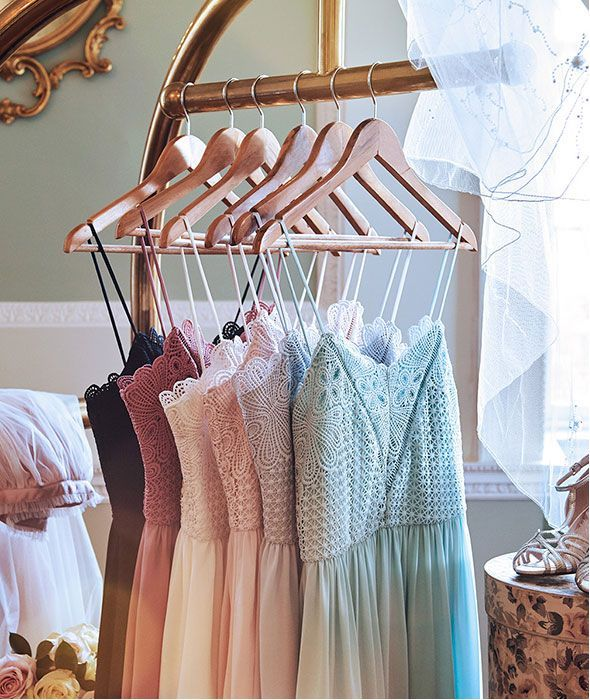 Collection of pastel and navy strappy bridesmaid dresses on hangers