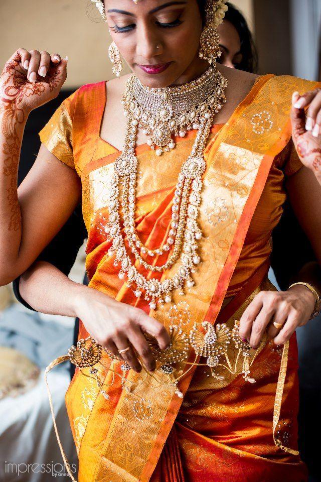Bride in Orange Saree Putting on Her Gold Belt Hindu