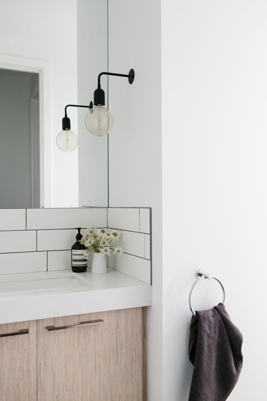 simple bathroom design subway tiles pendant light wooden cupboards minimalist bathroom