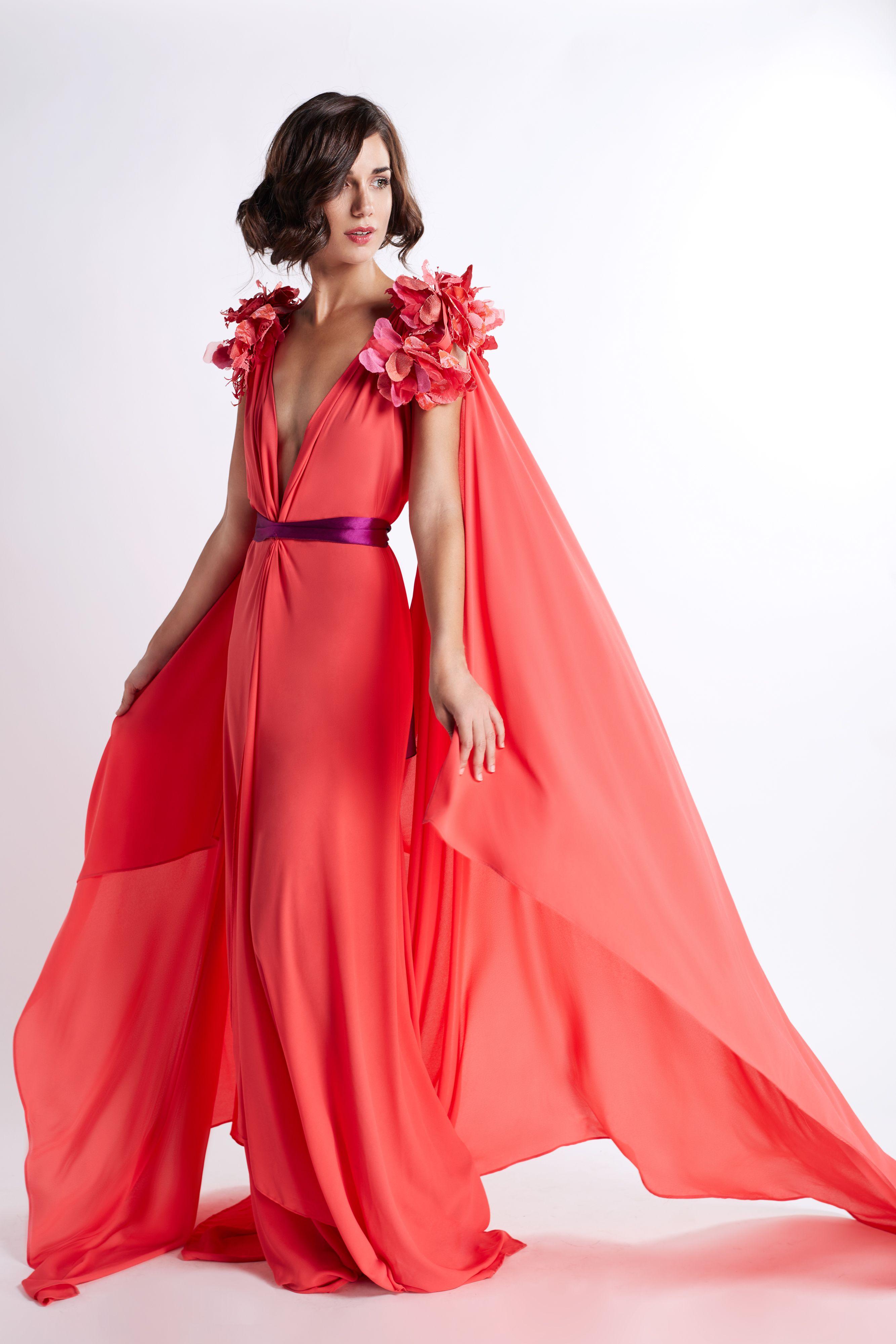 d3dbbc90c7f Vestido en color coral con escote en pico, vuelo y capa, con hombreras de  flores. Fajín en color morado para acentuar la cintura.