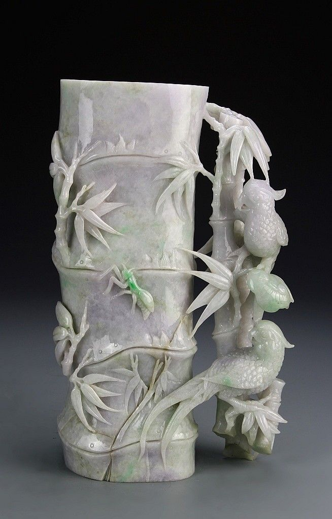 Description: China, carved jadeite brush pot, a pale purple color, intricately carved in a natural bamboo form with leaves, two birds sit upon an attached tree branch looking back on a green, carved insect. Height 11 1/2 in.