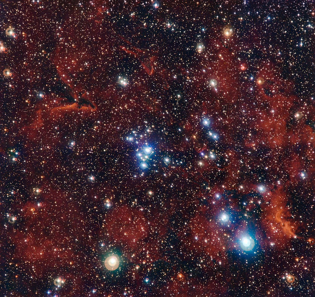A cluster of bright, young blue stars shows up vividly against the red hydrogen gas of their surrounding stellar birthplace in a stunning photo out just in time for the Fourth of July.