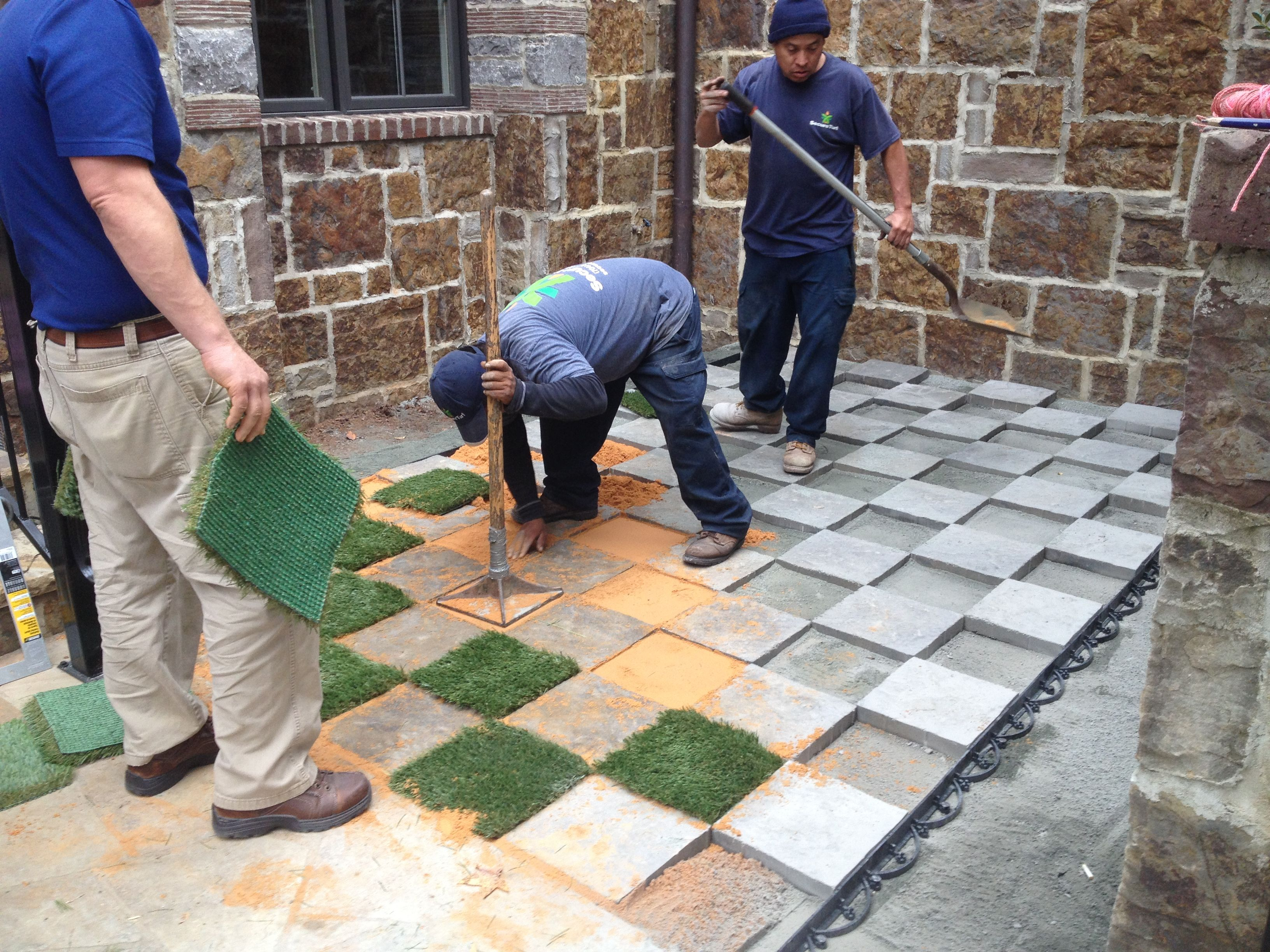 sand and turf is being installed pavers and artificial turf used
