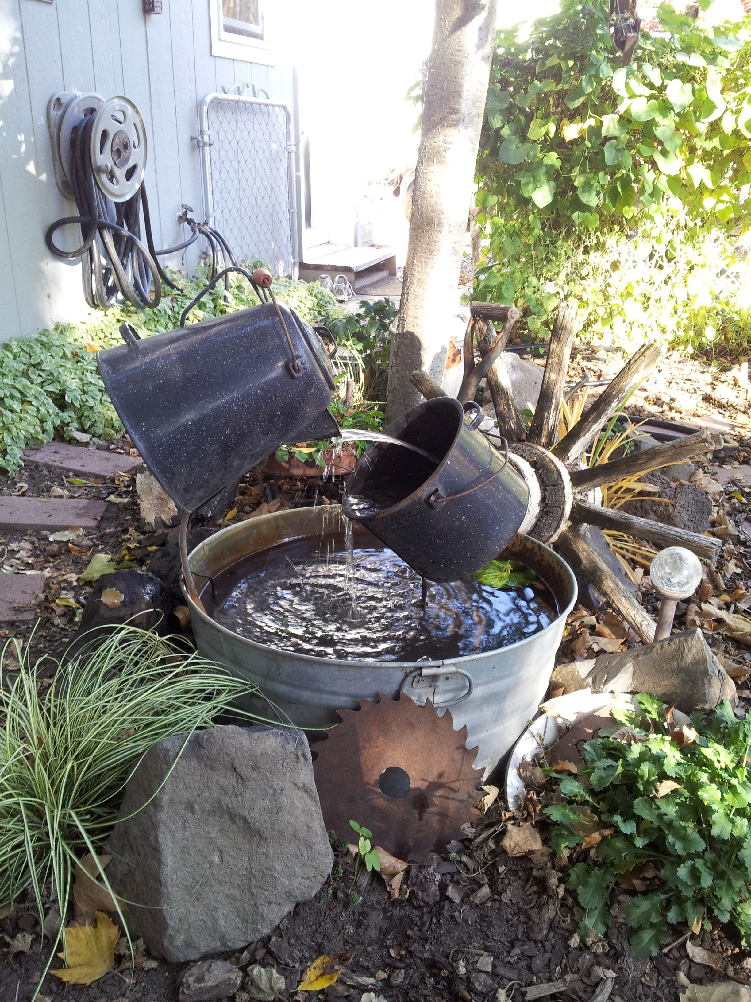 Garden fountain made from an old wash tub a big old coffee pot