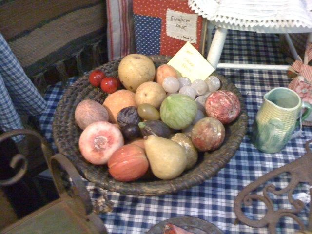 Bowl of antique marble fruit in Indian rye basket in old green paint.
