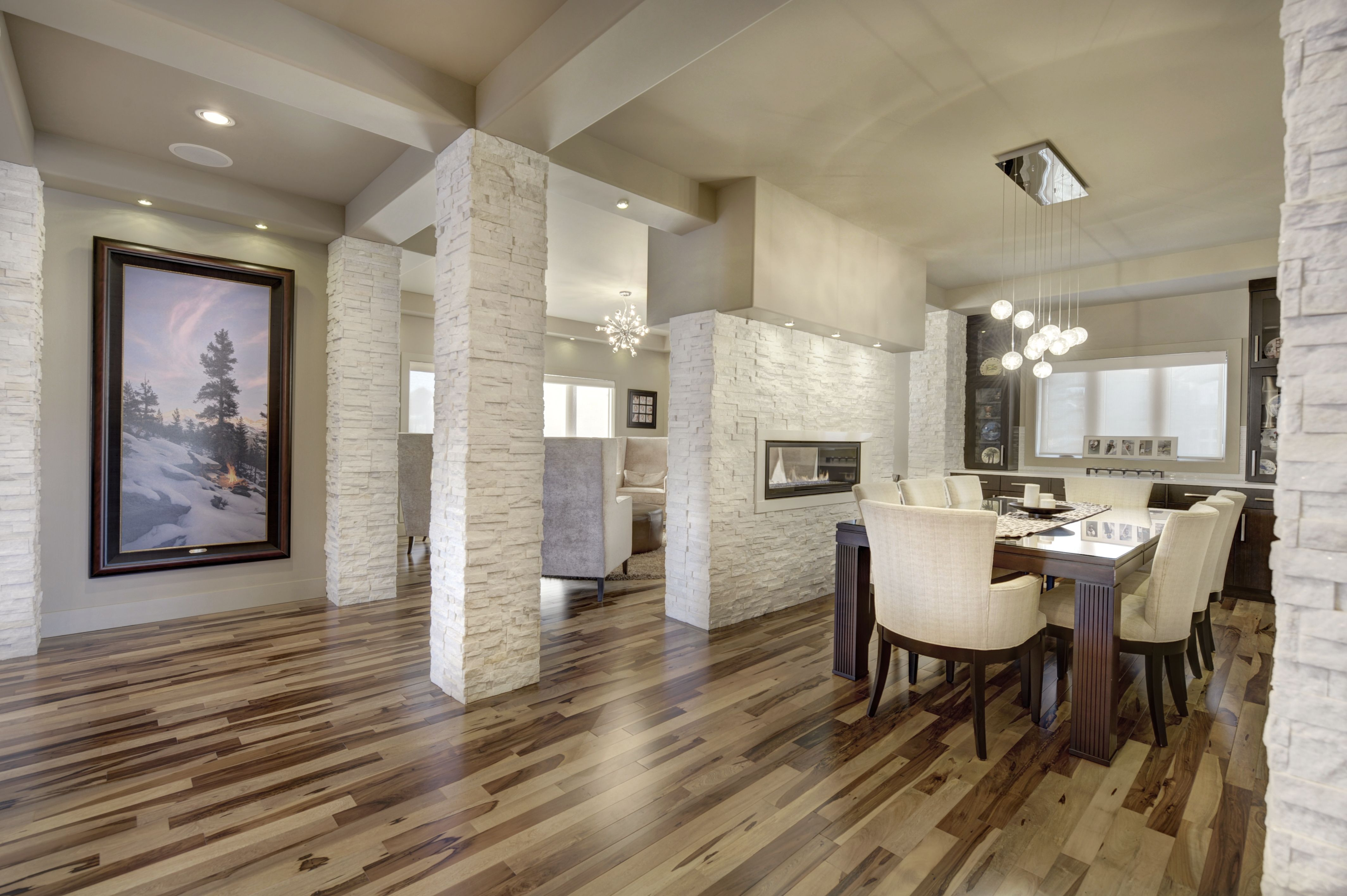Dining room with hardwood floors, white stone wall ...