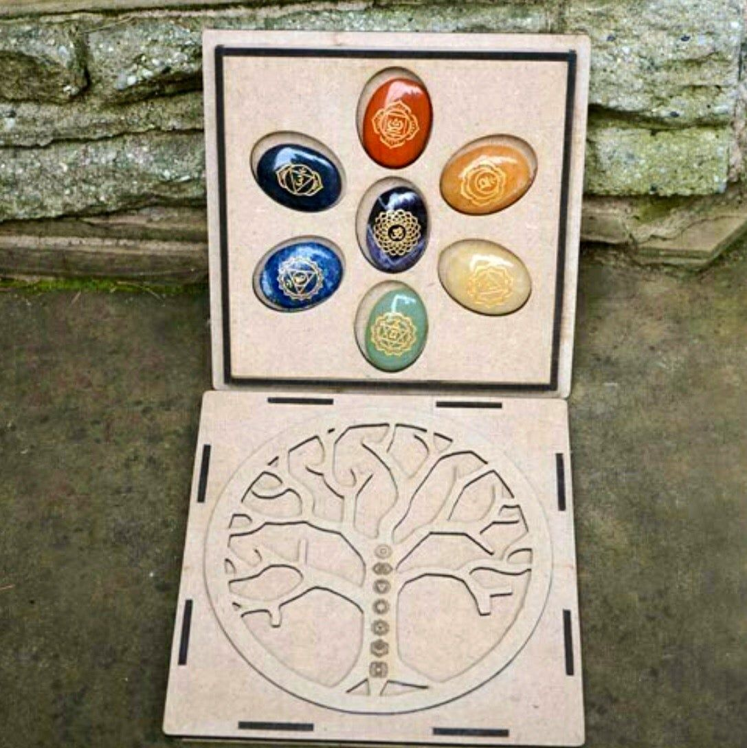 A complete 7 chakra stone set in a wood burned carved box