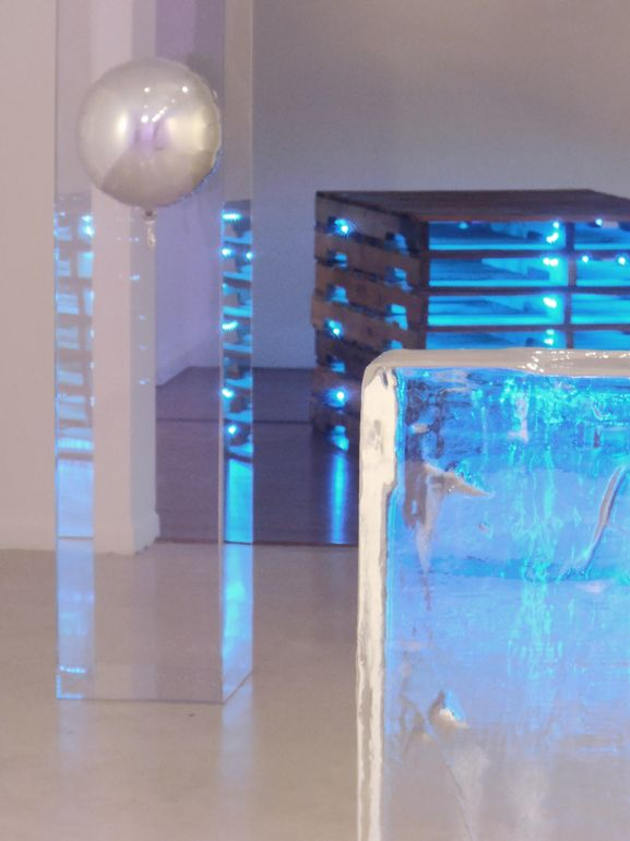 Zeitgeber, Peter Hammar  Installation: Mixed Media  Size: 14 H x 14 W x 72 in  300lbs Ice cubicle, pallet and bucket  Plexiglas, helium balloon and electrical fan  antique pallets and LED-Lights  Keywords: antique pallets, LED-Lights, helium balloon, 300lbs Ice cubicle, status quo