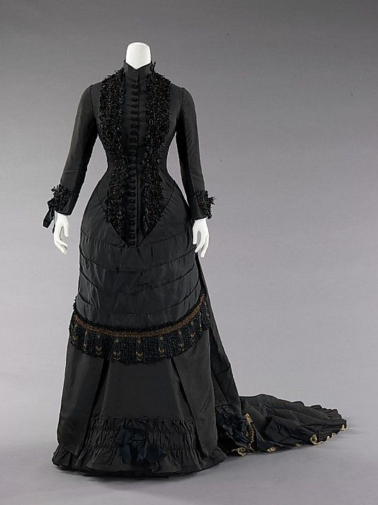 Spanish Dinner Dress (c. 1880) This historically inspired look is 72 inches long, made of silk and metal. This ensemble is an example of how darker colors were considered fashionable along with the built up puff in the back of the dress which provides more drama to the bustle silhouette and was a trendsetting look for this period.