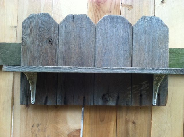 Shelf made from old fence boards and old, painted wrought