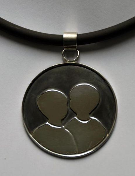 Zilveren medaillon met 2 kindersilhouetjes gemaakt door edelsmid Marja Schilt. www.marjaschilt.nl