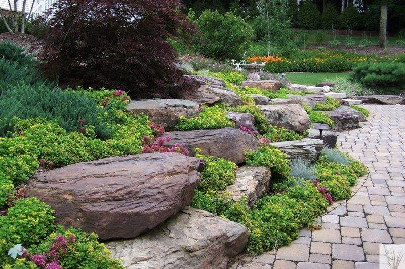 Stone outcropping, Sedum groundcover, and brick pavers Installed by