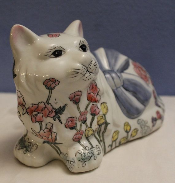 An inventive way to picture a little cat sitting in the garden - paint the flowers on the cat figurine, along with a blue ribbon, creating a