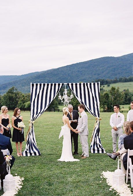 A preppy navy-and-white striped fabric altar with a hanging chandelier, created by Urban Lace Events.