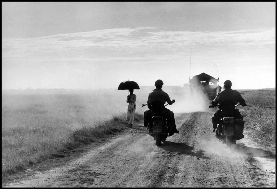 Robert Capa :  VIETNAM. May 25, 1954. Motorcyclists and woman walking on the road from Nam Dinh to Thai Binh.