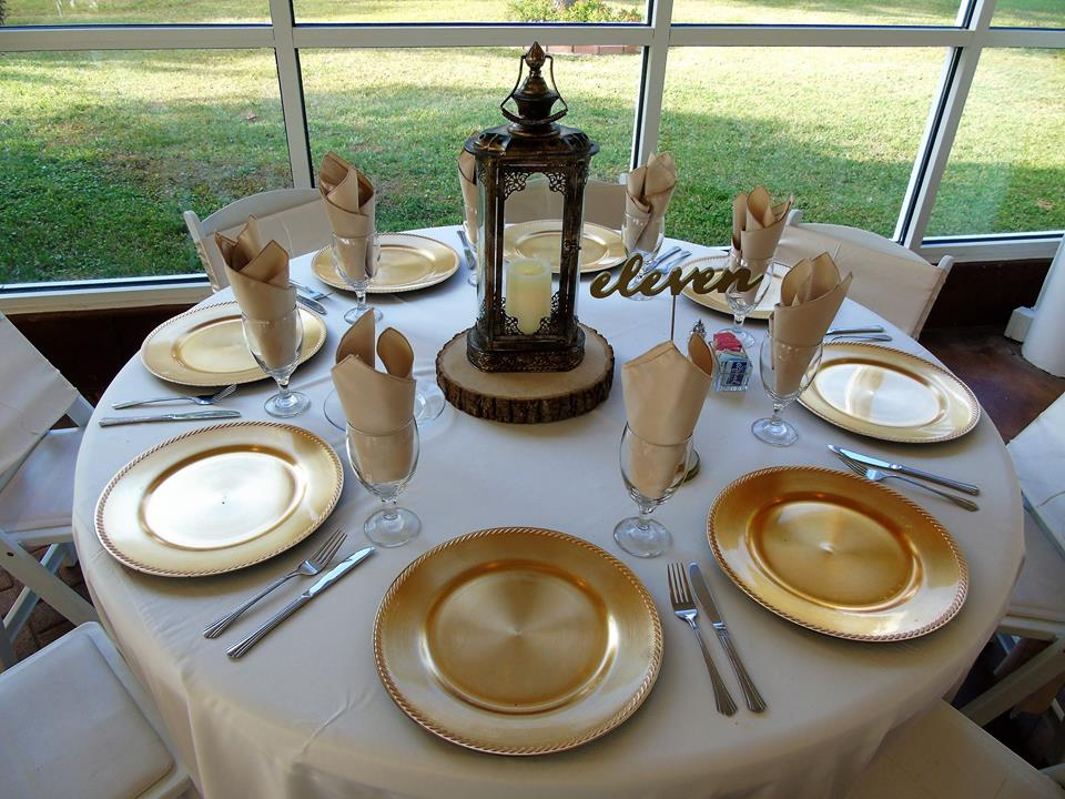 Table settings with gold chargers and lantern centerpieces ...