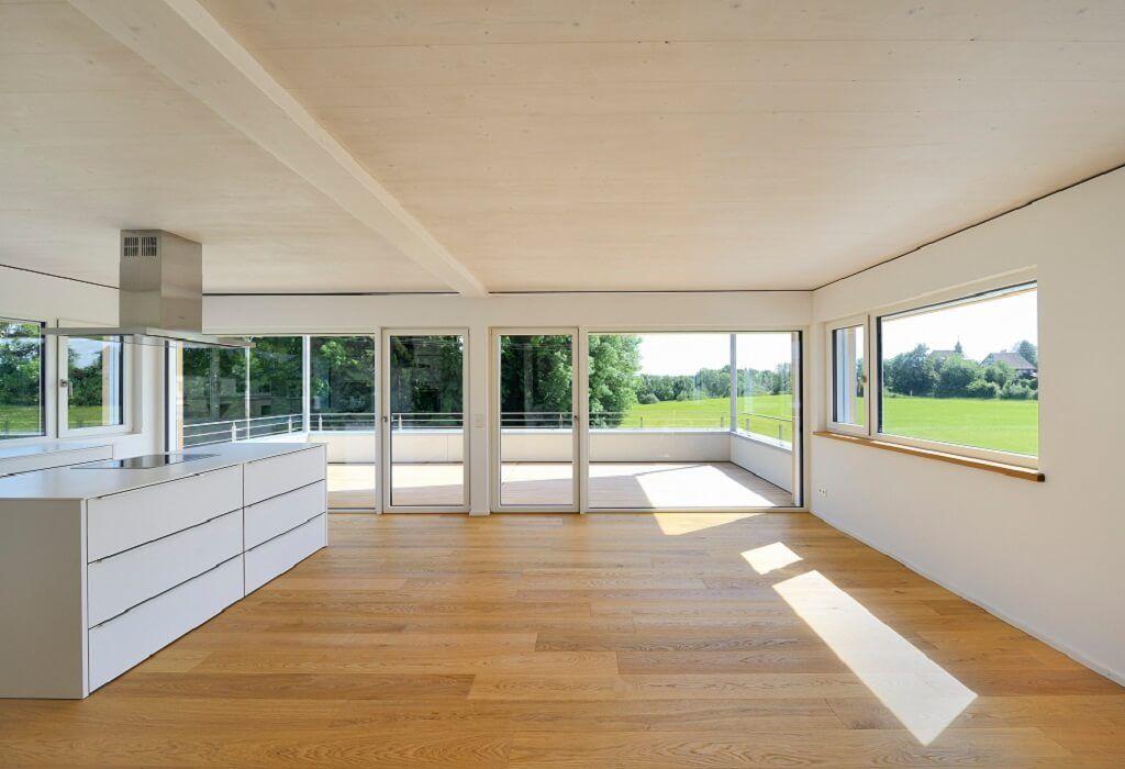 Innenraum Wohnzimmer mit offener Küche - Mehrfamilienhaus Erstling