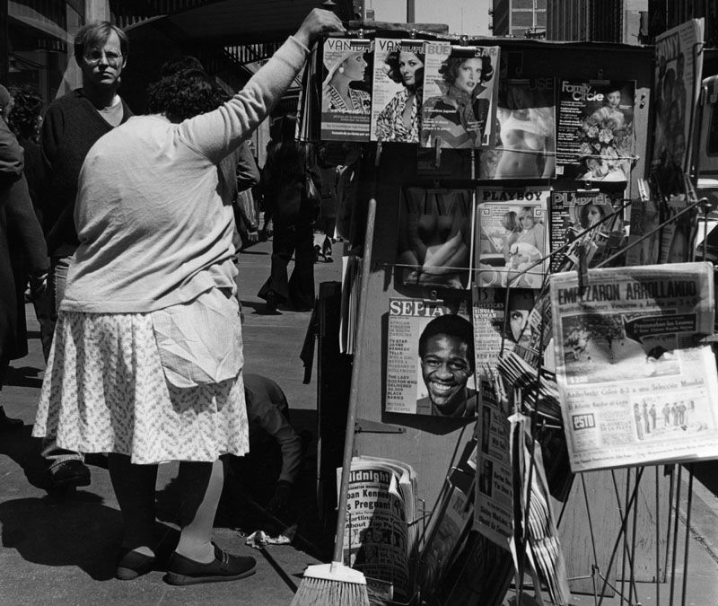 A newstand on the sidewalk on Broadway in downtown Los Angeles, displaying magazines and newspapers in English and Spanish, probably in 1979. (Photo credit: William Reagh / Los Angeles Public Library)