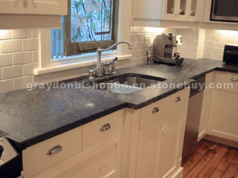 White kitchen cabinetry with soapstone countertops and a ...