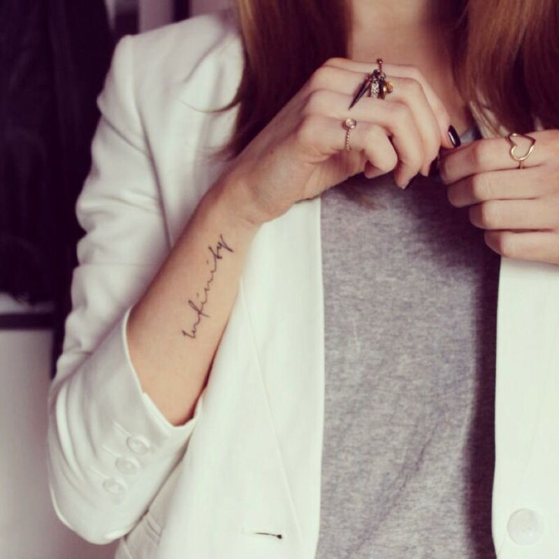 Infinity text tattoo and white blazer