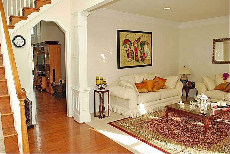 Pillars divide the entrance hall from the carpeted living room.