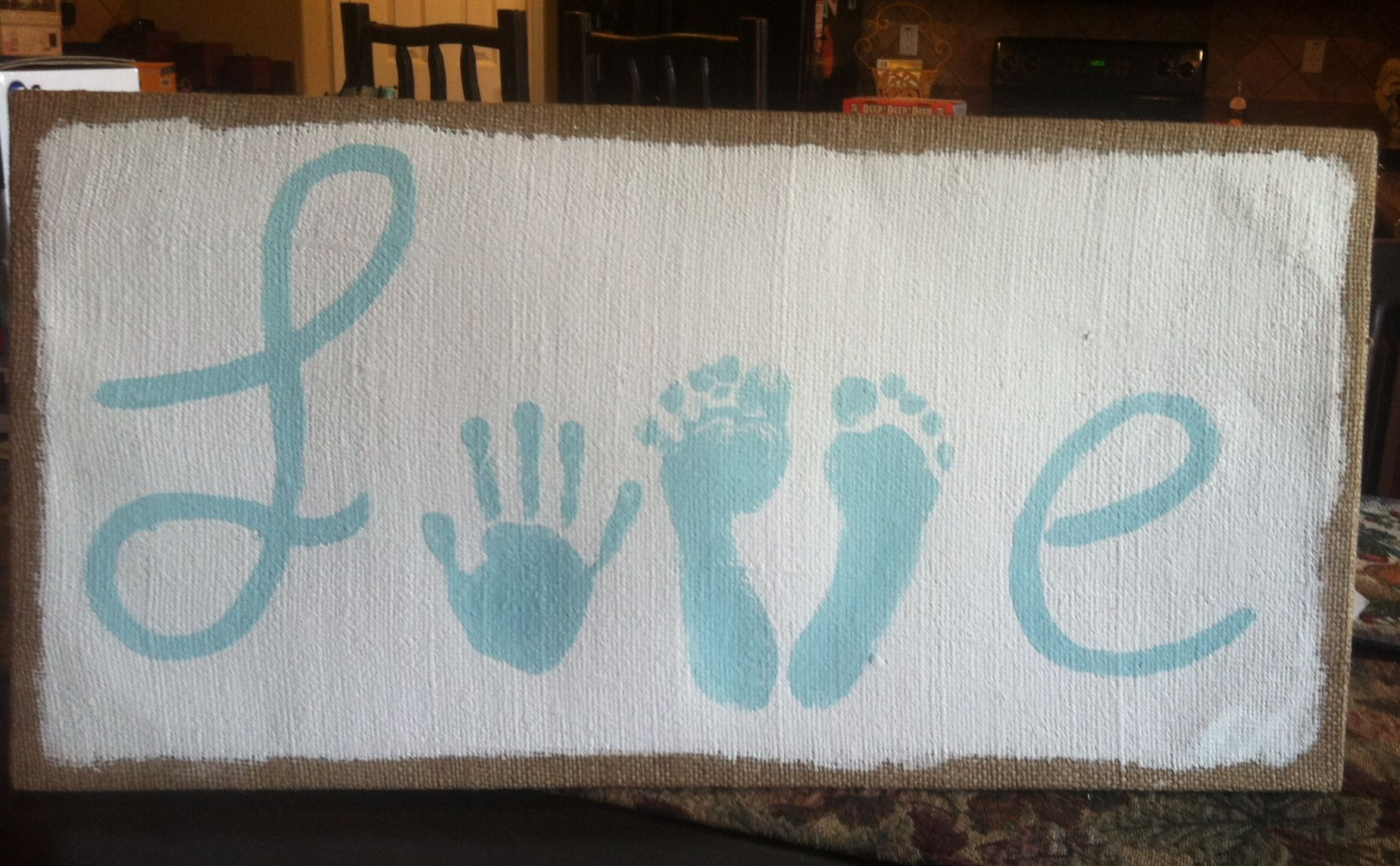 Love sign. Found this cool burlap canvas at hobby lobby. Painted my little girls hand and feet prints with acrylic paint in spa blue!! Love how it turned out!