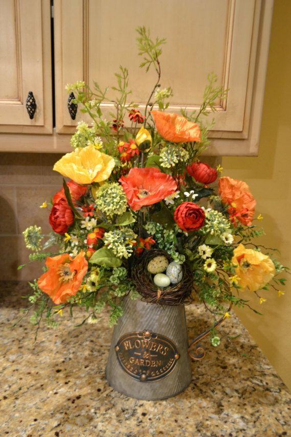 Dress up your table with this colorful arrangement! It is full of beautiful poppies and other pretty flowers and greenery with a nest on the side. It is made in a metal pitcher and measures approx. 15 x 23.