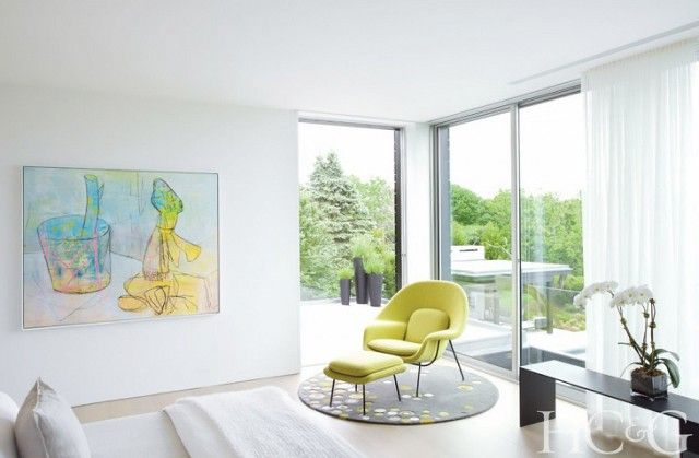 Neutral bedroom with large windows, colorful art, and a yellow statement armchair