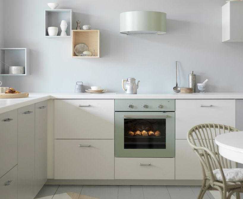 Grijsgroene afzuigkap en oven in een witte keuken met witte ...