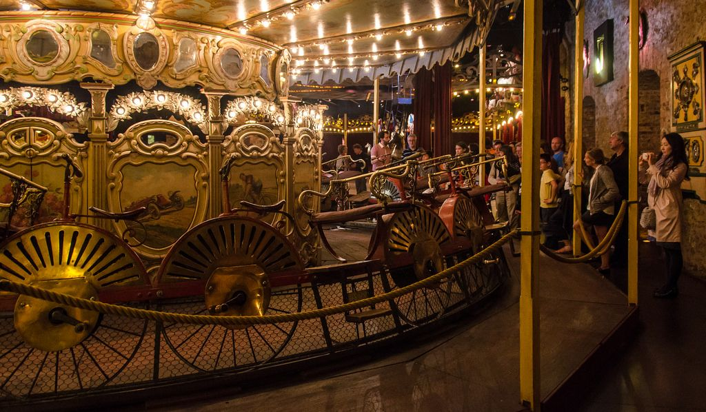 Tour guide leading people onto bicycle carousel, Musee des