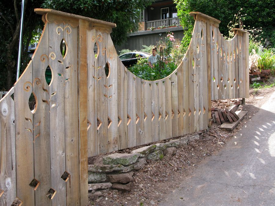 undulating lines of a recycled cedar art fence tackle a steep slope with the addition of stone