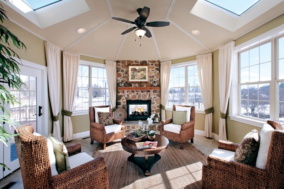 This sunroom features a stone fireplace with a wood mantel for Sunroom with fireplace