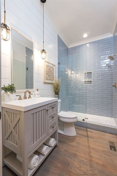 Photo of Coastal Farmhouse bathroom with shiplap walls, store-bought vanity and hardwood …