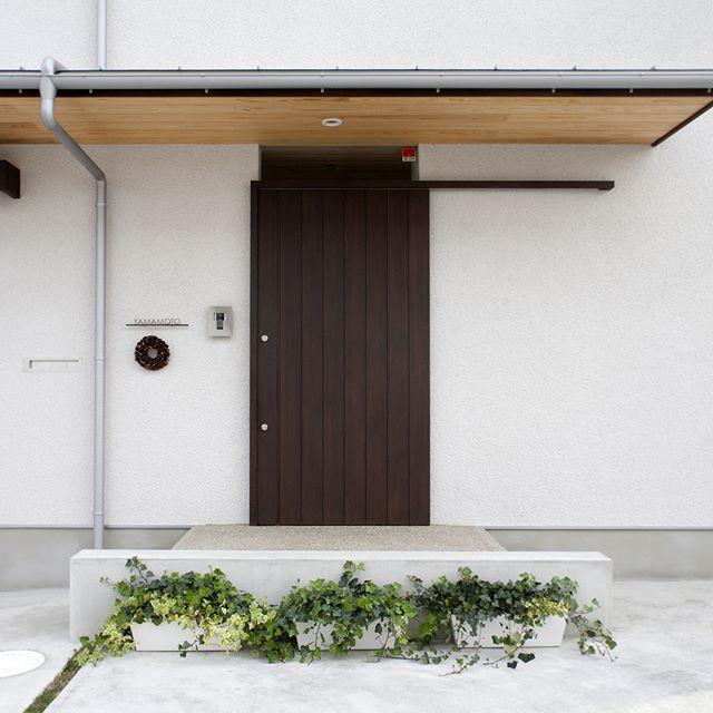 プランターの緑を輝かせる そとん壁の玄関 平屋 注文住宅 新築