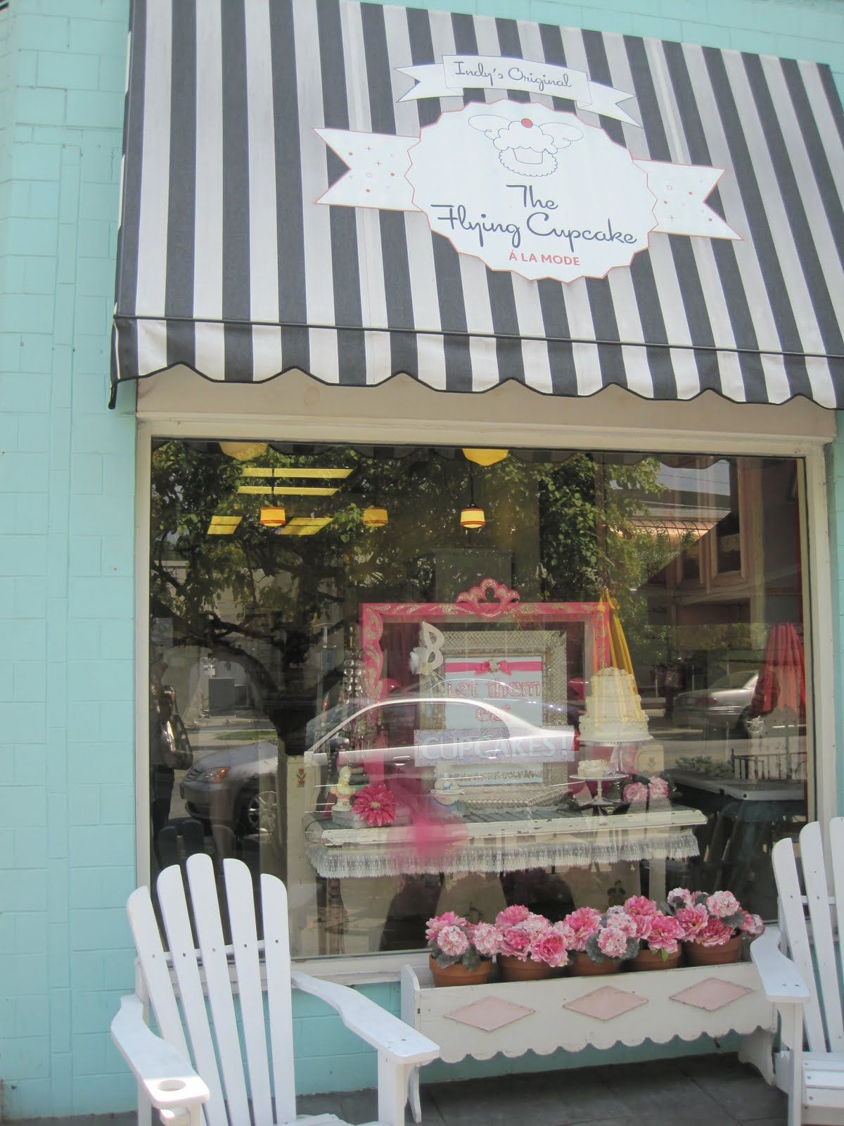 Love the striped awning and use of color. The white chairs and flowers really add some character to.