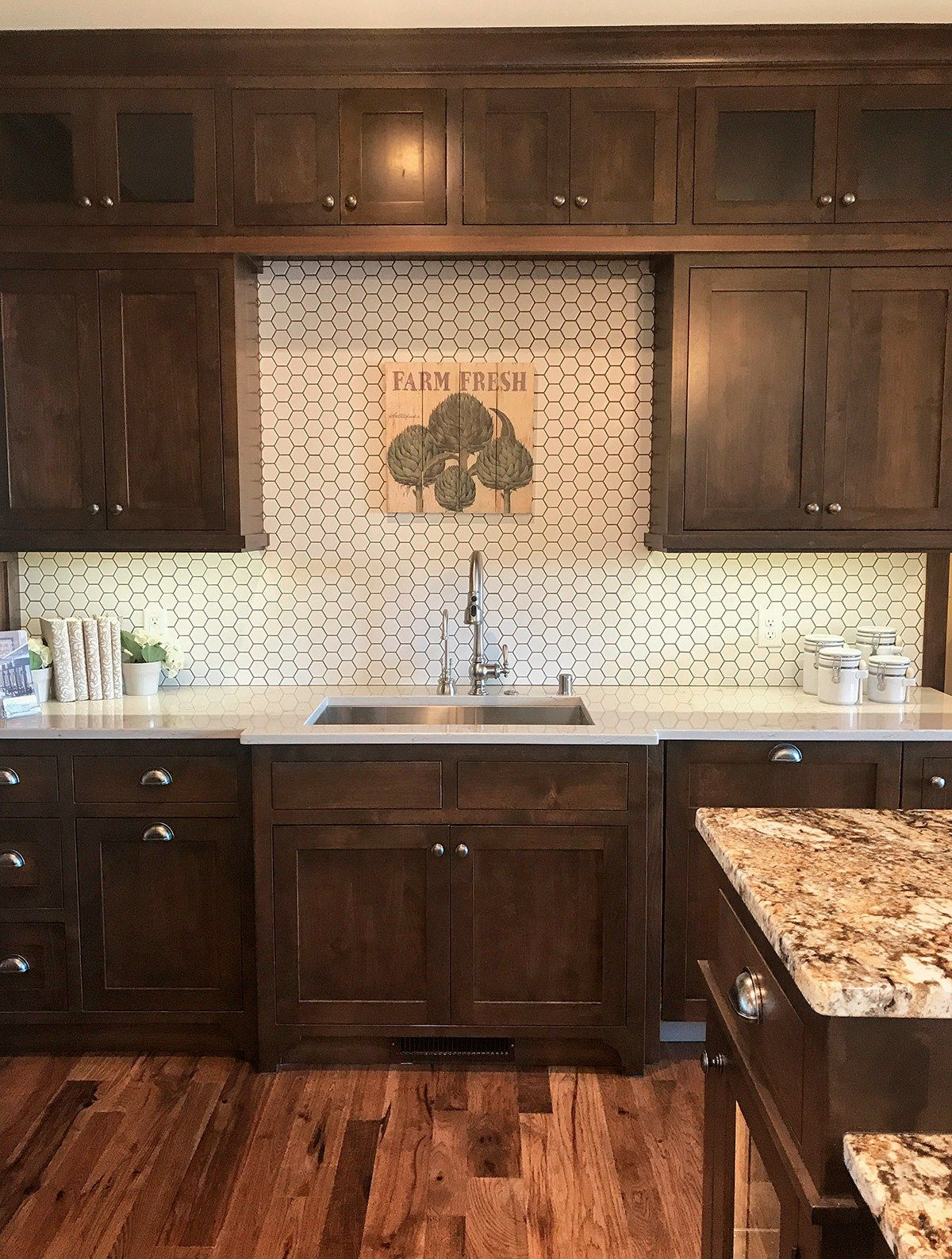 Backsplash trends great contrast in this kitchen warm brown cabinets rustic wood floors granite white hexagon tile with dark grout