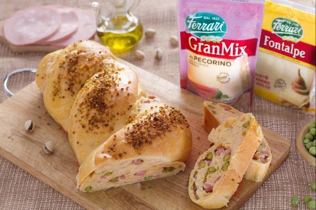 Il pane intrecciato ripieno è una preparazione rustica, una treccia salata ripiena di piselli, prosciutto cotto e formaggio ideale per l'aperitivo.