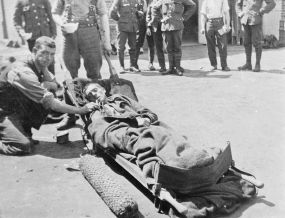 A seriously gassed case being given oxygen outside the North Midland Field Ambulance, Hazebrouck, June 1915.  Q 51886