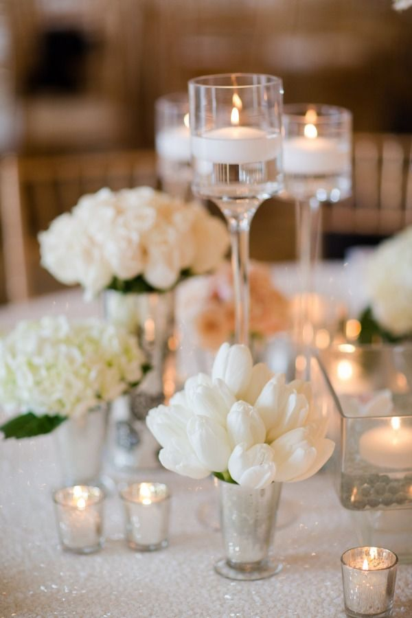 A simple yet stunning low centrepiece idea. High stemmed votives surrounded by different white floral arrangements in silver julep cups.