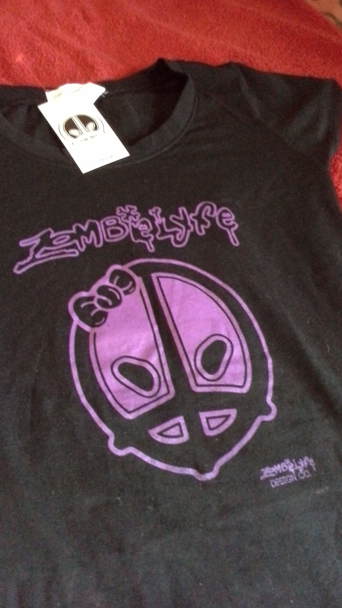 "Black women's Zombielyfe tshirt. Purple print in plastisol ink. 95% cotton and 5% spandex. Tshirt is hand signed by the designer on the back of the shirt under the neckline. $20.00 plus shipping fee ""hunger for knowledge"" www.zombielyfe.com instagram: kingthesis"
